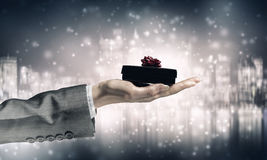 Woman presenting gift box . Mixed media Stock Images