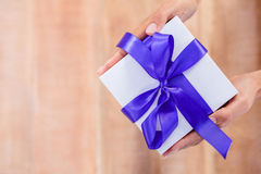 Woman presenting gift with purple ribbon Royalty Free Stock Image