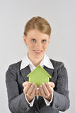Woman presenting a green house. Red haired businesswoman presenting a green house Royalty Free Stock Photos