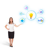 Woman presenting light bulb with colorful graphs. Young woman presenting light bulb with colorful graphs and diagrams isolated on white Royalty Free Stock Photo