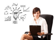 Woman presenting light bulb with diagrams. Young business woman presenting light bulb with various diagrams and charts on whiteboard isolated on white Stock Photos