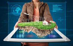 Woman presenting a perfect ecology land with a house and windmil Royalty Free Stock Photos
