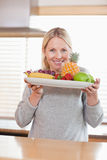 Woman presenting plate of fruits Royalty Free Stock Images
