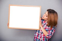 Woman presenting something on a blank board Royalty Free Stock Photos