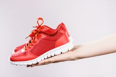 Woman presenting sportswear trainers shoes. Woman presenting sportswear trainers red shoes, comfortable footwear perfect for workout and training Stock Images