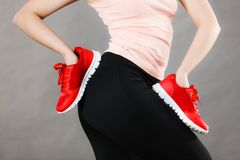 Woman presenting sportswear trainers shoes. Woman presenting sportswear trainers red shoes, comfortable footwear perfect for workout and training Royalty Free Stock Images