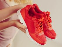 Woman presenting sportswear trainers shoes. Sporty woman presenting sportswear trainers red shoes, comfortable footwear perfect for workout and training Royalty Free Stock Photo