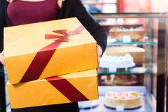 Woman presenting takeaway boxes of confectionery Stock Photos