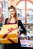 Woman presenting takeaway boxes of confectionery Royalty Free Stock Image