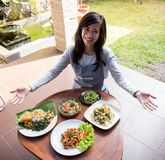 Woman presenting various indonesian food. Beautiful asian woman presenting various indonesian food on a table royalty free stock photography