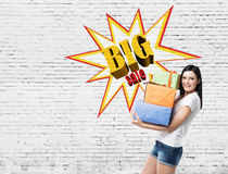 Woman with presents near a brick wall with big sale poster Stock Photography