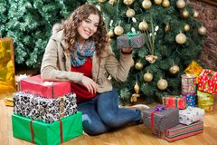 Woman With Presents Sitting Against Christmas Tree Royalty Free Stock Image