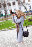 Woman press photographer shooting in city Royalty Free Stock Photo