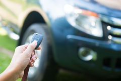 Woman pressed on the remote to open the car Royalty Free Stock Photography