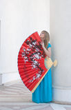 The woman presses to itself the big fan Stock Photography