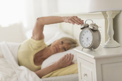 Woman Pressing Button Of Alarm Clock While Lying In Bed royalty free stock photo