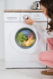 Woman Pressing Button Of Washing Machine Stock Image