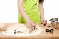 Woman pressing christmas molds in dough Stock Photography