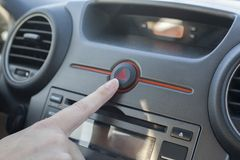 Woman pressing hazard lights button. Inside car view royalty free stock photography