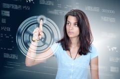 Woman pressing high tech type of modern buttons on a virtual bac. Young woman pressing high tech type of modern buttons on a virtual background Royalty Free Stock Photos