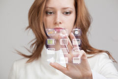 Woman pressing high tech type of modern multimedia. Young businesswoman pressing high tech type of modern multimedia buttons on a virtual background Stock Image
