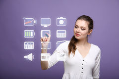 Woman pressing multimedia and entertainment icons on a virtual background Royalty Free Stock Image