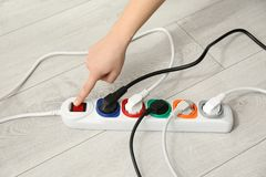Woman pressing power button of extension cord on floor. Closeup. Electrician`s professional equipment stock images