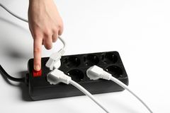 Woman pressing power button of extension cord on white background, closeup. Electrician`s equipment stock photography