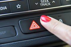 Woman pressing red triangle car hazard warning button. Female finger hitting car emergency light botton royalty free stock image