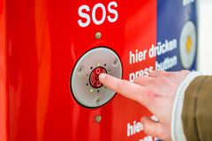 Woman pressing SOS emergency button in train station. Only finder to be seen royalty free stock image