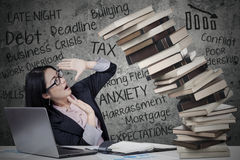 Woman with pressure and collapsing books Royalty Free Stock Image
