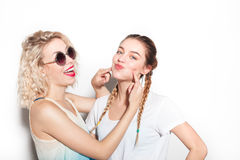 Woman pressuring on friend`s cheeks Royalty Free Stock Images
