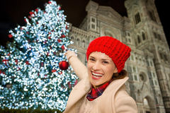 Woman pretend decorating Christmas tree in Florence, Italy. Happy young woman decorating Christmas tree near Duomo with Christmas ball. She enjoying Christmas stock image