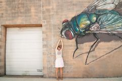 A woman pretending a huge graffiti fly is eating her. Winter Street Studios in Houston,Texas, USA. June 2018 Stock Photos