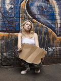 Woman Pretending To Beg Against Brick Wall. Portrait of a young woman squatting by brick wall pretending begging Stock Image