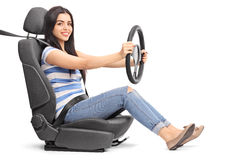 Woman pretending to drive seated on a car seat. Young cheerful woman pretending to drive seated on a car seat isolated on white background Royalty Free Stock Photography