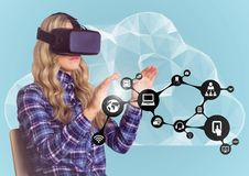 Woman pretending to touch while wearing virtual reality headset against cloud interface background Stock Photo