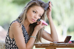 Woman with pretty face do her makeup outside Royalty Free Stock Photo