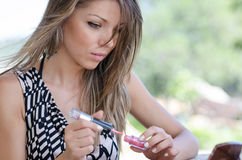 Woman with pretty face do her makeup outside Stock Photography