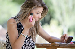 Woman with pretty face do her makeup outside Stock Images