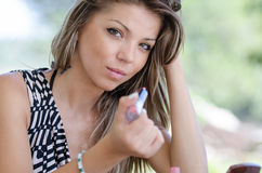 Woman with pretty face do her makeup outside Stock Photo