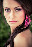 Woman pretty with pink. Beautiful brunette model with her long hair pinned into a pink floral clip gazing with her dark brown eyes over her naked shoulder stock image
