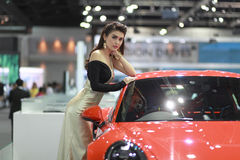 Woman. A pretty women is posing near car brand Porsche stock photo