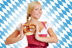 Woman with pretzel in a dirndl. Smiling attractive woman with pretzel in a dirndl in front of Bavarian flag royalty free stock image