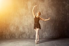 Woman prima theater  dance. Young beautiful woman prima theater in a black pack, white pantyhose, white pointe shoes beautifully dances Russian ballet in a black Stock Photo