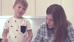 Woman primary class tutor teaches little boy. Front view - attractive young woman primary class tutor teaches little boy sitting at table on background of white stock video