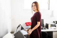 Woman printing labels in a plotter Royalty Free Stock Photo