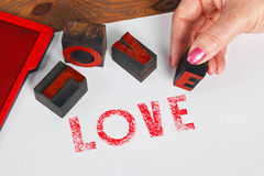 Woman printing LOVE using wooden letterpress Royalty Free Stock Photos