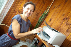 Woman printing on the printer stock images