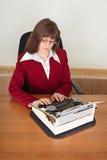 Woman prints on an ancient typewriter Stock Photos